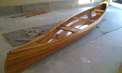"""Brand new cedar canoe.  Red Bird, by Ted Mores design from canoe craft. Western Red Cedar & Epoxy/Fiberglass sheathing. Keel, Deck, Inwhale & Outwhale are Ash. Seat frames are Ash. Woven canoe seats. Inlaid with walnut & ash. Lenght = 17'6"""" Weight is"""